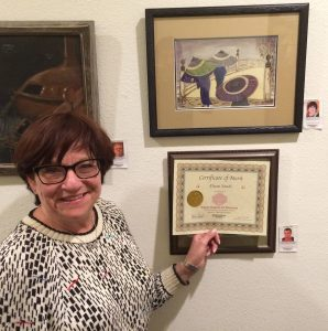 Diane Sands receives a Certificate for her acrylic painting, Pastimes for a Lifetime Student Art Showcase