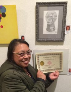 Dorothy Gamoning receives a Certificate for her graphite work, Pastimes for a Lifetime Student Art Showcase