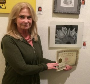 Ginny Lieberman receives a Certificate for her chalk pastel work, Pastimes for a Lifetime Student Art Showcase