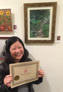 Reiko Nakashima receives a Certificate for her acrylic painting, Pastimes for a Lifetime Student Art Showcase