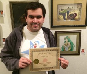 Robbie Jager receives a Certificate for his colored pencil work, Pastimes for a Lifetime Student Art Showcase