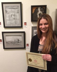 Taylor Vlahos receives a Certificate for her graphite work, Pastimes for a Lifetime Student Art Showcase