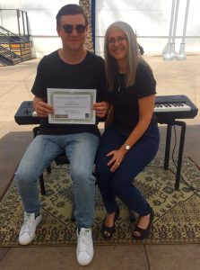 Pastimes for a Lifetime piano student Cameron C receives a certificate of merit for his performance at the Downtown Burbank Arts Festival