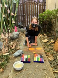 Pastimes for a Lifetime art student Sophie R paints chalk pumpkins on the studio sidewalk for the Fall SSCAI