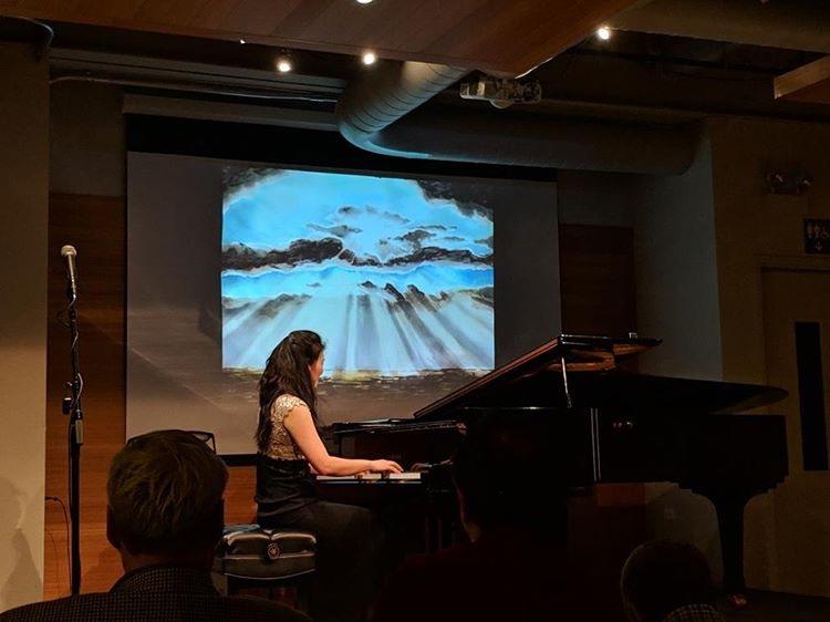 Jeeyoon Kim plays piano while Moonsub Shin's artwork is displayed