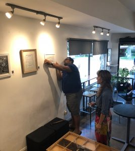 Pastimes for a Lifetime art student Sumeet V., and office manager Jessica Lee Sanders help install the 2019 Fall Student Art Showcase
