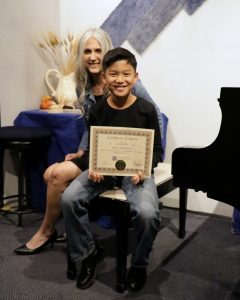 Ascher C. receives a COM from piano teacher Linda Wehrli