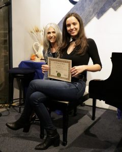 Katie S. receives a Certificate of Merit from piano teacher Linda Wehrli