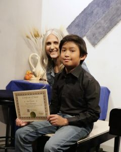 Ryan B. receives a certificate of merit from piano teacher Linda Wehrli