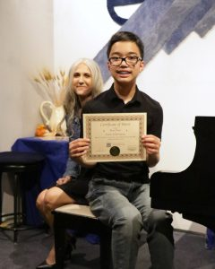 Ryan P. receives a certificate of merit from piano teacher Linda Wehrli