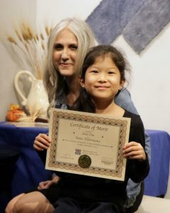 Zoie C. receives a Certificate of Merit from piano teacher Linda Wehrli
