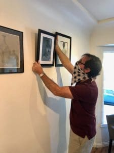 Barry Michael Wehrli helps install student artwork at the M Street Coffee Gallery Student Showcase