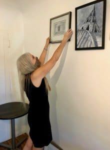 Linda Wehrli installs student artwork at the M Street Coffee Virtual Gallery Showcase